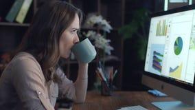从杯子的想法的女实业家饮用的茶和看屏幕 影视素材