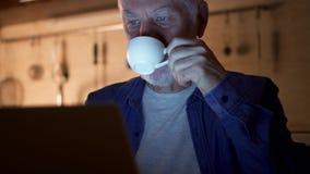 从杯子的老人饮用的咖啡,当使用膝上型计算机时 自由职业者在运作从家庭办公室的晚上 股票录像
