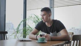 从杯的年轻人饮用的咖啡 在netbook的自由职业者工作在现代coworking 在遥远的工作的程序员 股票视频