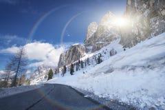 从柏油路的风景冬天视图在用雪和树盖的山在a的路一边 库存图片