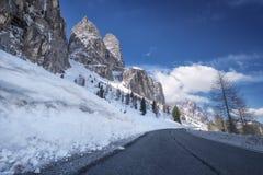 从柏油路的风景冬天视图在用雪和树盖的山在a的路一边 免版税库存照片