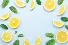 从柠檬切片和薄荷叶的框架在蓝色淡色台式视图 夏天饮料和柠檬水的成份 平的位置样式 库存图片
