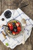 从格兰诺拉麦片,香草chia布丁,草莓,在一块大服务的玻璃的蓝莓的一顿健康早餐快餐在a 免版税库存图片