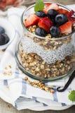 从格兰诺拉麦片,香草chia布丁,草莓,在一块大服务的玻璃的蓝莓的一顿健康早餐快餐在a 免版税库存照片
