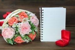 从桃红色和橙色玫瑰、婚戒和一本白皮书的婚礼花束在木背景的拷贝空间的 库存照片