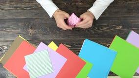 从桃红色纸的人折叠的origami 影视素材