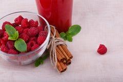 从桃红色莓果的一份健康饮料在轻的布料背景 一个碗用莓、薄菏和桂香在书桌上 库存图片