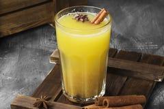 从桔子和香料的冬天热的饮料在黑背景 库存图片