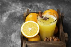 从桔子和香料的冬天热的饮料在黑背景 免版税库存图片