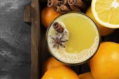 从桔子和香料的冬天热的饮料在黑背景 免版税库存照片