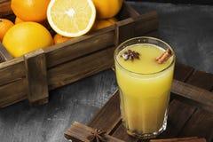 从桔子和香料的冬天热的饮料在黑背景 库存照片