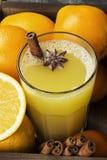 从桔子和香料的冬天热的饮料在黑背景 图库摄影