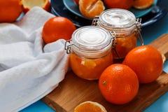 从桔子的甜果酱在小瓶子用新鲜的桔子 免版税库存图片