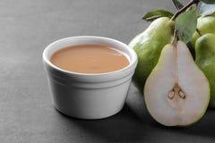 从梨和新鲜的成熟梨的纯汁浓汤在一张黑桌上的裁减 库存照片