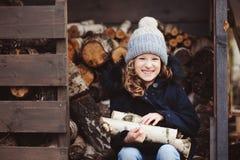 从棚子的愉快的儿童女孩采摘木柴在冬天 库存图片