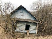 从森林的老蓝色老被毁坏的木被放弃的被破坏的蓝色村庄房子 免版税库存图片