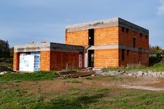 从橙色砖建造的未完成的家庭房子 免版税库存照片