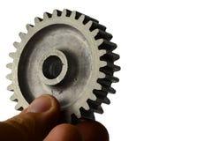 从正齿轮的有一点使用的alluminium合金嵌齿轮轮子在白色背景的左手举行了 免版税库存照片