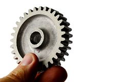 从正齿轮的有一点使用的alluminium合金嵌齿轮轮子在白色背景的左手举行了 免版税库存图片