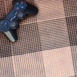 从比赛控制台的电子游戏控制器在方格的沙发 控制的无线电设备在电子游戏期间 免版税库存照片