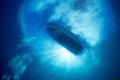 从水下的蓝色海洋的小船船有太阳的发出光线 库存照片