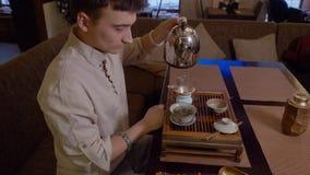 从水壶的人倾吐的面汤在碗用干茶,当传统仪式时 股票录像
