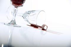 从水晶葡萄酒杯的溢出的红葡萄酒 库存照片