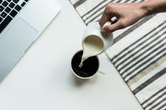 从水罐的人倾吐的牛奶到杯子无奶咖啡里 图库摄影