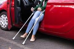 从汽车出来的残疾妇女 免版税库存照片