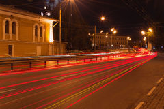 从汽车前灯的红色轨道在桥梁在晚上 免版税图库摄影