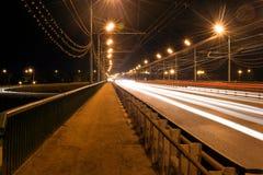 从汽车前灯的红色轨道在桥梁在晚上 库存照片