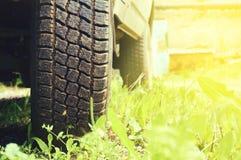 从汽车特写镜头转动反对绿草背景  抽象背景 免版税库存图片