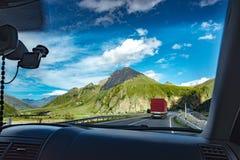 从汽车的看法,路、夏天山绿草和蓝天环境美化 免版税库存照片