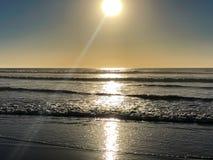 接踵而来的海浪和阳光反射从沙滩在阿加迪尔,摩洛哥,非洲日落的 免版税库存照片