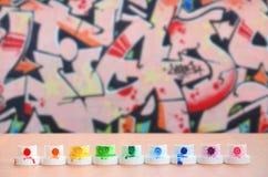 从油漆喷雾器的被弄脏的多彩多姿的喷管在色的街道画图画背景的一张木桌上排队  免版税图库摄影
