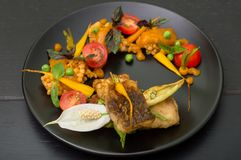 从油煎的鱼的盘用扁豆、绿豆、杏子调味汁、嫩胡萝卜和西红柿 黑色木背景 库存照片