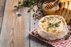 从法国的真正的软制乳酪用麝香草、蜂蜜和敬酒的面包在老木土气桌上 在木背景wi的软干酪 免版税库存照片