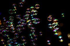 从泡影吹风机的肥皂泡在黑暗或黑背景中 库存照片