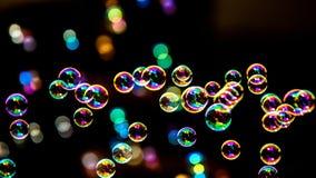 从泡影吹风机的肥皂泡在黑暗或黑背景中 库存图片