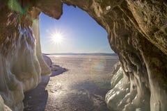 从洞穴的看法有冰冰柱、太阳和blye天空的大块和小丘的 自然本底 库存图片