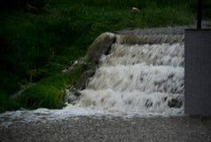 从流动在台阶下的圆鼓的小河的水 库存照片
