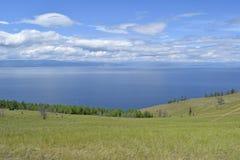 从海岛的绿色倾斜的美丽的贝加尔湖 免版税库存照片
