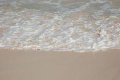 从海洋泡沫的透视图在沙子地面 免版税库存照片