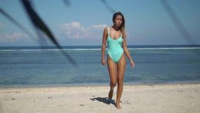 从海洋走出去跨步在白色的俏丽的性感的年轻女人送海滩 股票视频