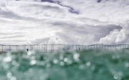 从海看见的冲浪者女孩有云彩背景 免版税图库摄影