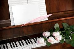 从淡粉红的玫瑰、音乐纸和白色空白纸的构成与在棕色钢琴的桃红色翎毛钢笔 免版税库存照片