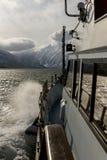 从游艇的弓的看法对堪察加山的 光束击穿日落云彩 暑假的概念海上的 免版税库存图片