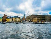 从游览小船的全景在奥斯陆王宫、游船和Gamla斯坦斯德哥尔摩瑞典江边房子  免版税库存照片
