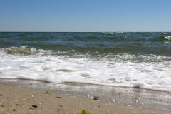 从湿沙子的海洋挥动 库存照片