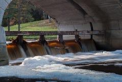 从溢出的小瀑布在一座石桥梁下 免版税库存图片